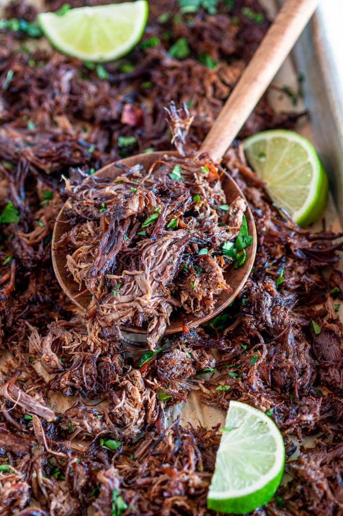 Instant Pot Barbacoa Beef on sheet pan and parchment paper spoonful with lime slices