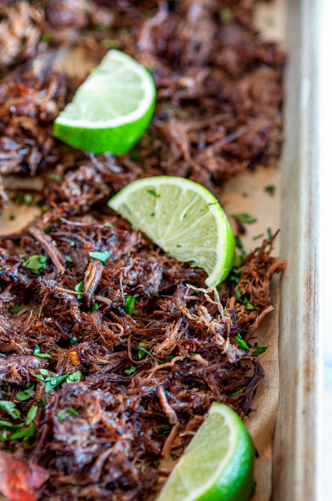 Instant Pot Barbacoa Beef on sheet pan and parchment paper with lime slices