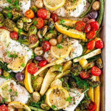 Sheet Pan Cod Vegetable Dinner with lemon slices on white marble