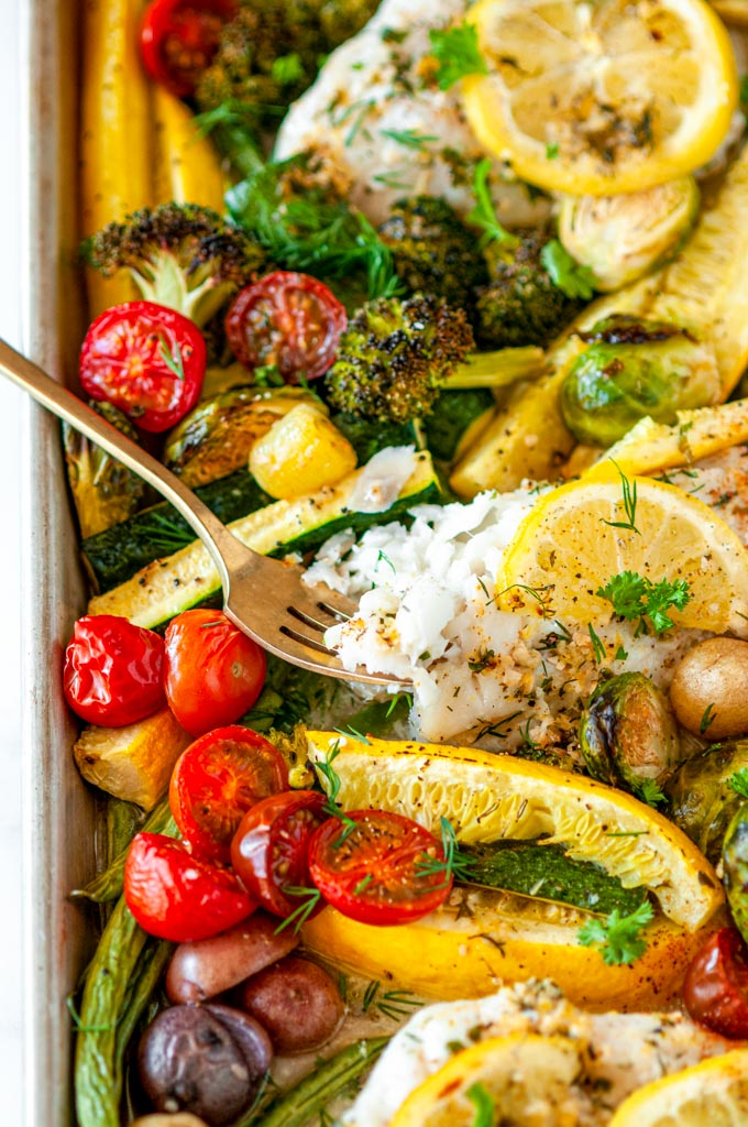 Sheet Pan Cod Vegetable Dinner with gold fork and lemon slices on white marble