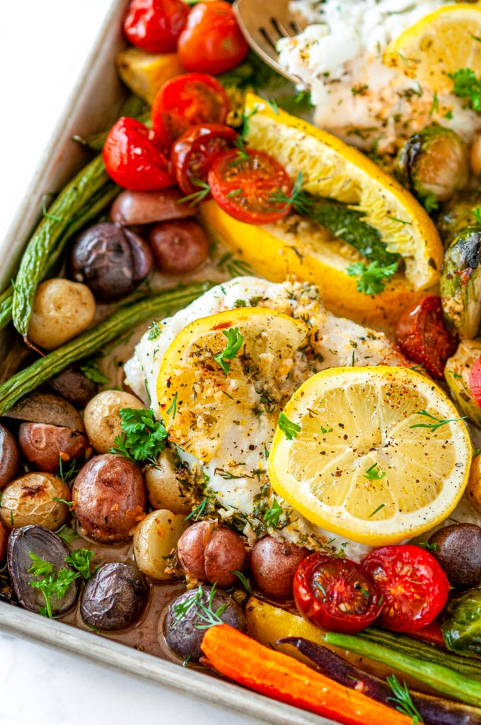 Sheet Pan Cod Vegetable Dinner with lemon slices on white marble