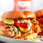 Panko Crusted Spicy Chicken Sandwiches with coleslaw, tomato, and pickles on white plate with hot sauce bottle in background