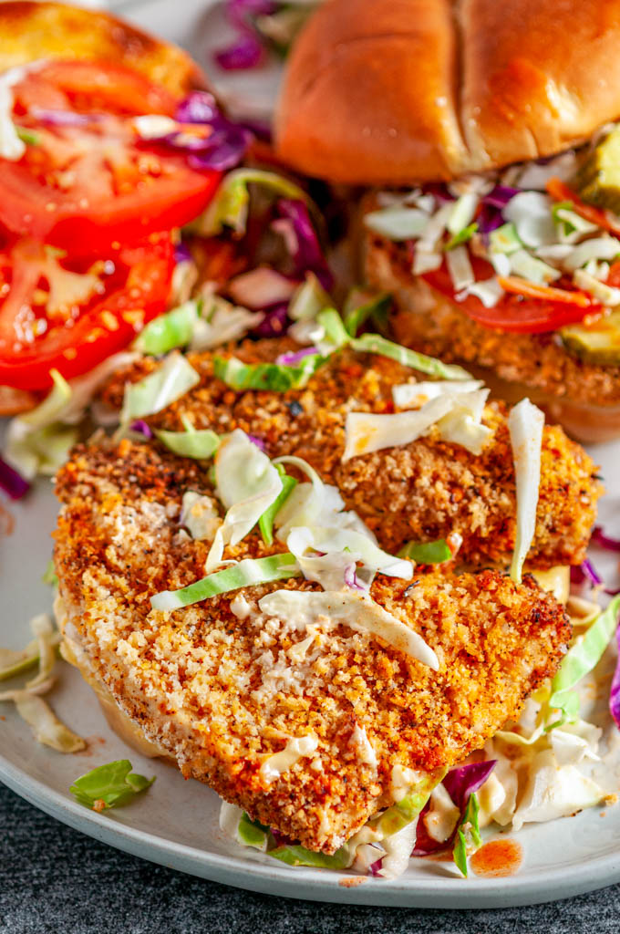 Panko Crusted Spicy Chicken Sandwiches open faced on white plate with coleslaw, tomato, and pickles