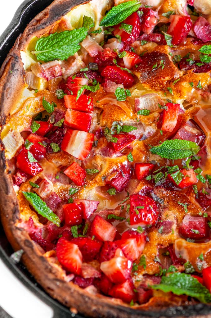 Strawberry Rhubarb Dutch Baby in lodge cast iron skillet with mint and lemon curd on white marble