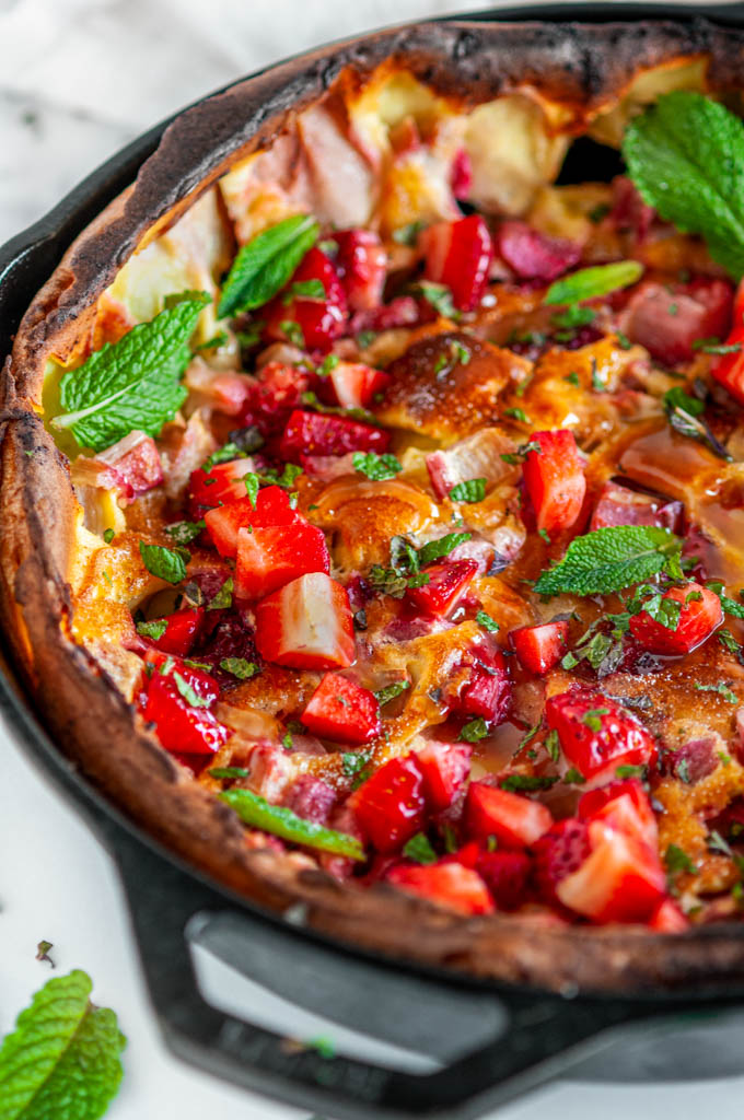 Strawberry Rhubarb Dutch Baby in lodge cast iron skillet with mint, lemon curd, and gold spoon on white marble