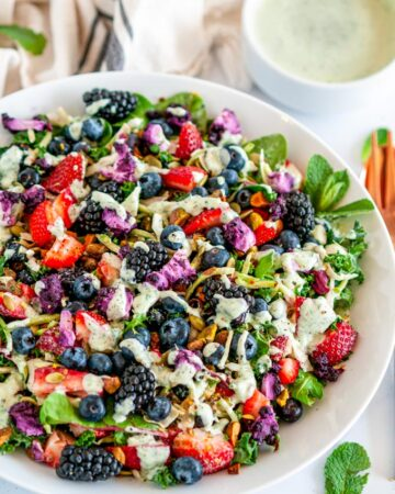 Superfood Berry Salad with Creamy Lemon Herb Dressing in white bowl on marble with copper dinnerware