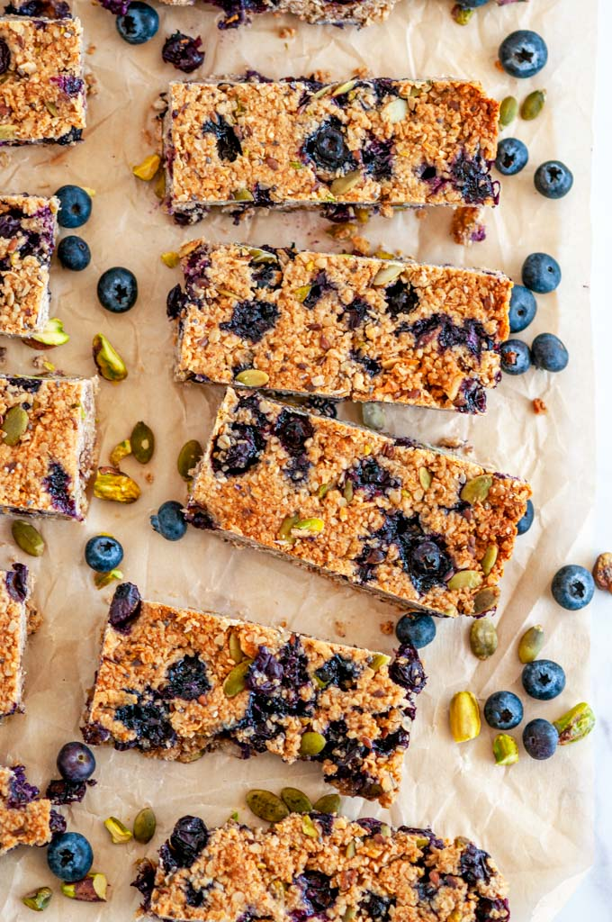 Blueberry Pistachio Coconut Granola Bars on parchment and white marble