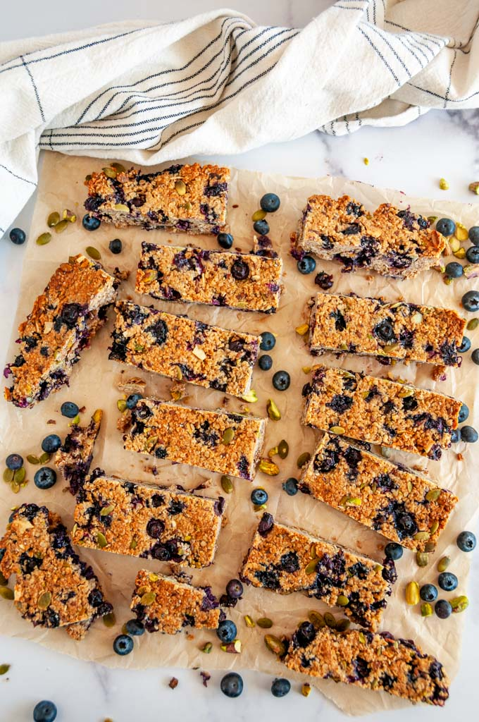 Blueberry Pistachio Coconut Granola Bars on parchment and white marble with tea towel