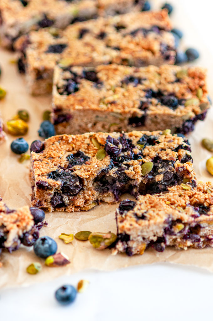 Blueberry Pistachio Coconut Granola Bars on parchment and white marble close up