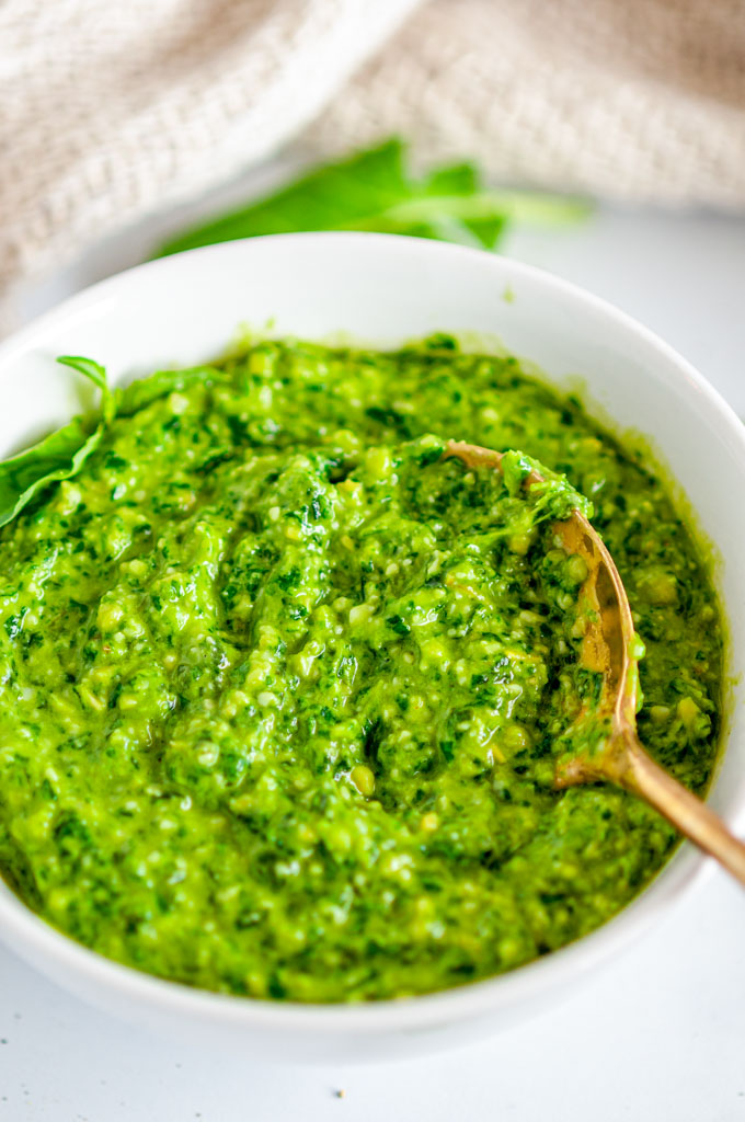 Easy Kale Basil Pesto in white bowl with gold spoon on white marble close up