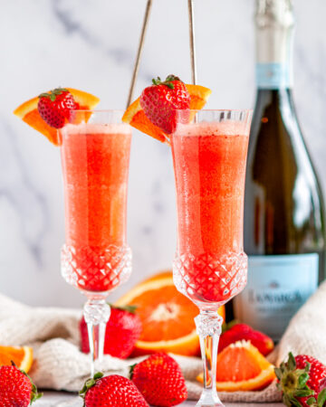 Sunrise Strawberry Mimosa Cocktail in glasses with oranges and Prosecco bottle in background on white marble