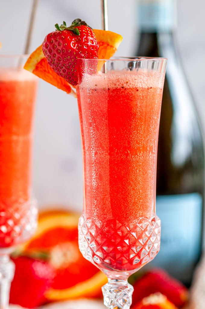 Sunrise Strawberry Mimosa Cocktail in glasses with oranges and Prosecco bottle in background