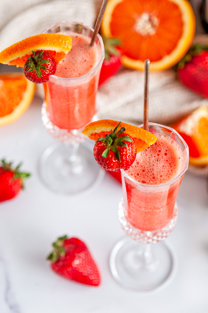 Sunrise Strawberry Mimosa Cocktail in glasses with oranges in background on white marble