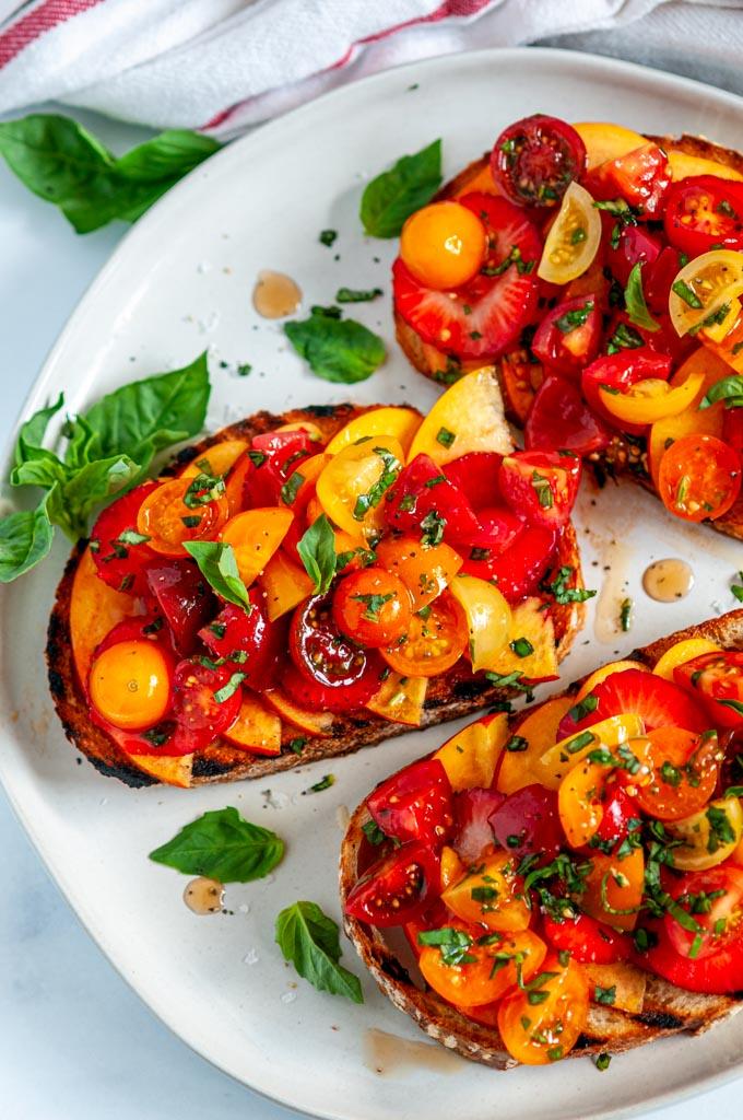 Nectarine Strawberry Tomato Bruschetta on gray plate with fresh basil on white marble
