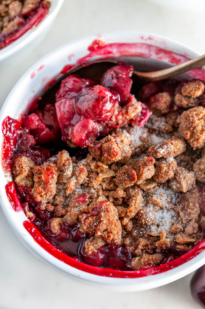 End of Summer Cherry Crumble in white ramekin with gold spoon on white marble