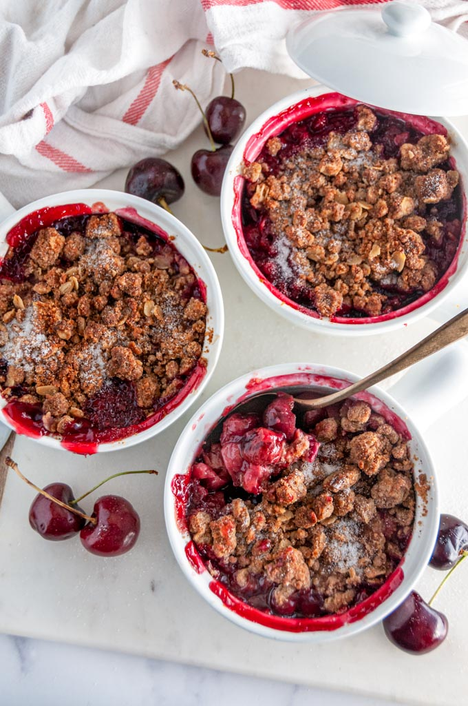 End of Summer Cherry Crumble in white ramekins with gold spoon and tea towel on white marble