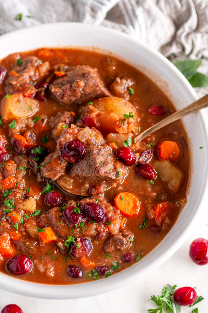 Cranberry Apple Beef Stew in white bowl with gold spoon and tea towel on white marble