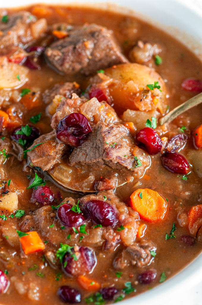 Cranberry Apple Beef Stew in white bowl with gold spoon on white marble