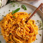 Pumpkin Fettuccini Alfredo on gray plate with copper fork on white marble