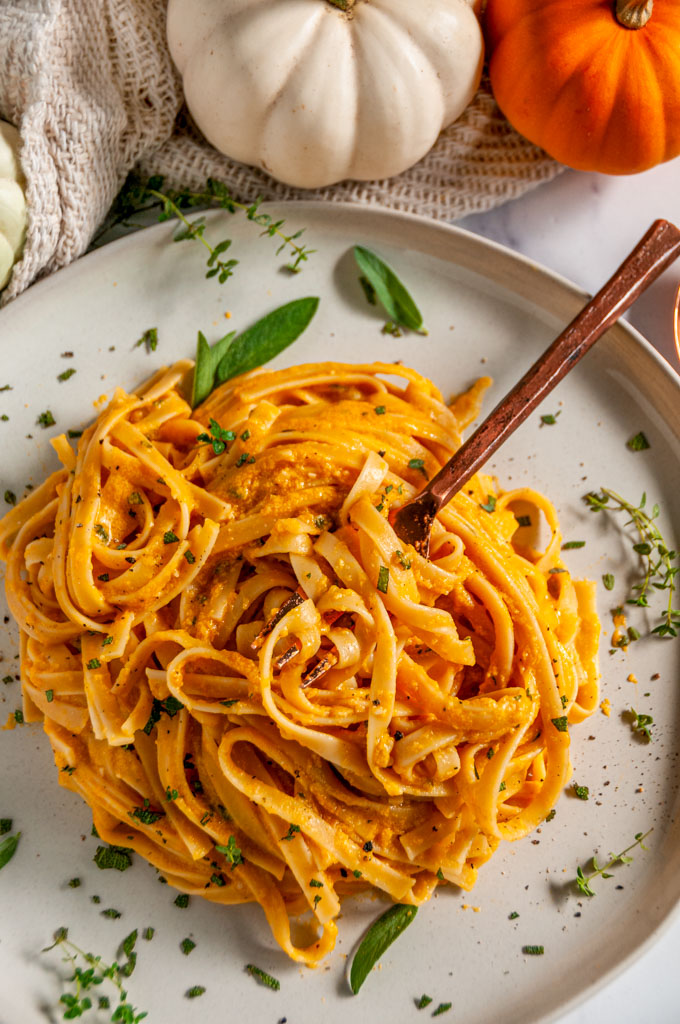 Pumpkin Fettuccine Alfredo on gray plate with copper fork on white marble